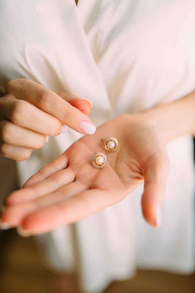 person holding a pair of earrings on her hands