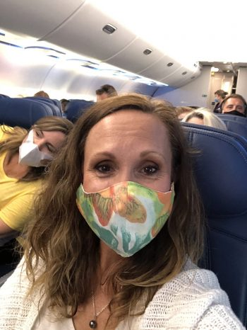 Tami Santini wearing face mask inside the airplane